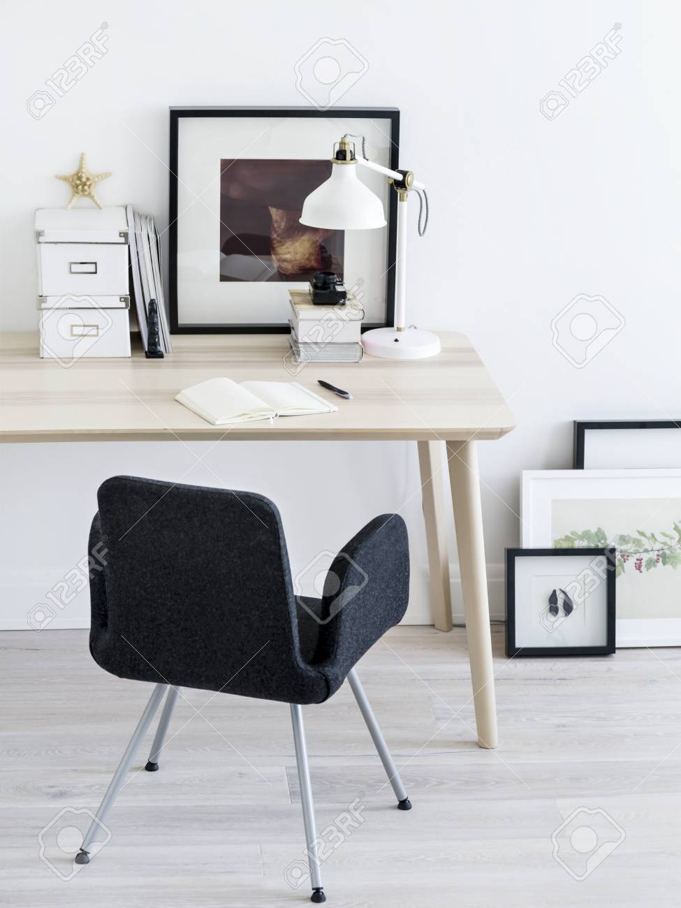 Comfortable chair standing near small table and nice frames pictures in stylish room stock photo