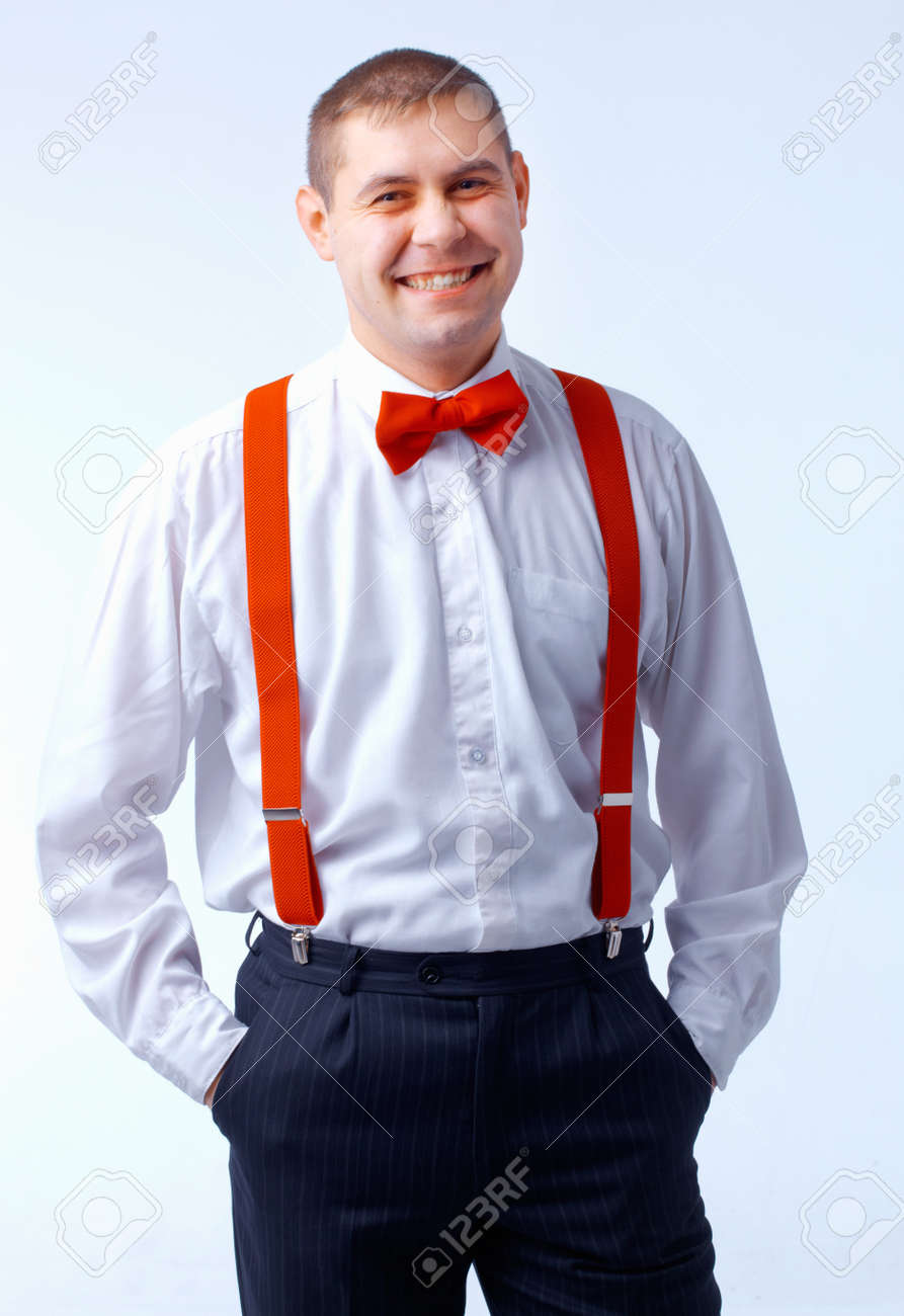 b7d5e73fef33 smiling man with red bow tie and braces standing with hands in pocket.  Stock Photo