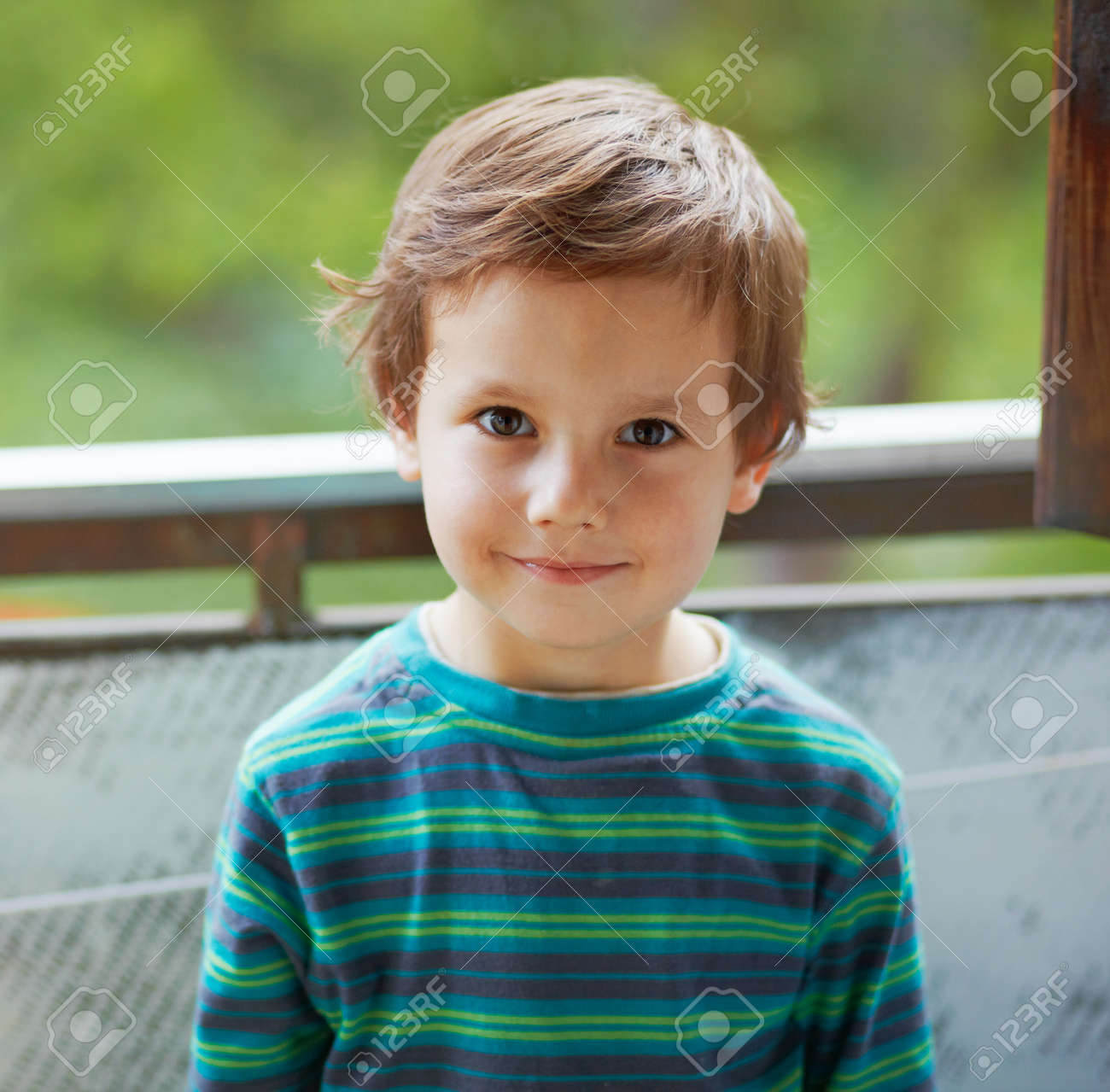 portrait of a small boy standing and smiling to you stock photo