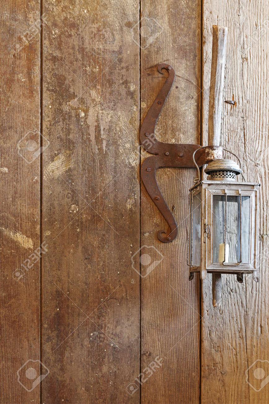 Una Puerta De Madera Hecha De Madera De Granero Con Lamparas Rusticas De Vela Vintage Colgando En El Mango
