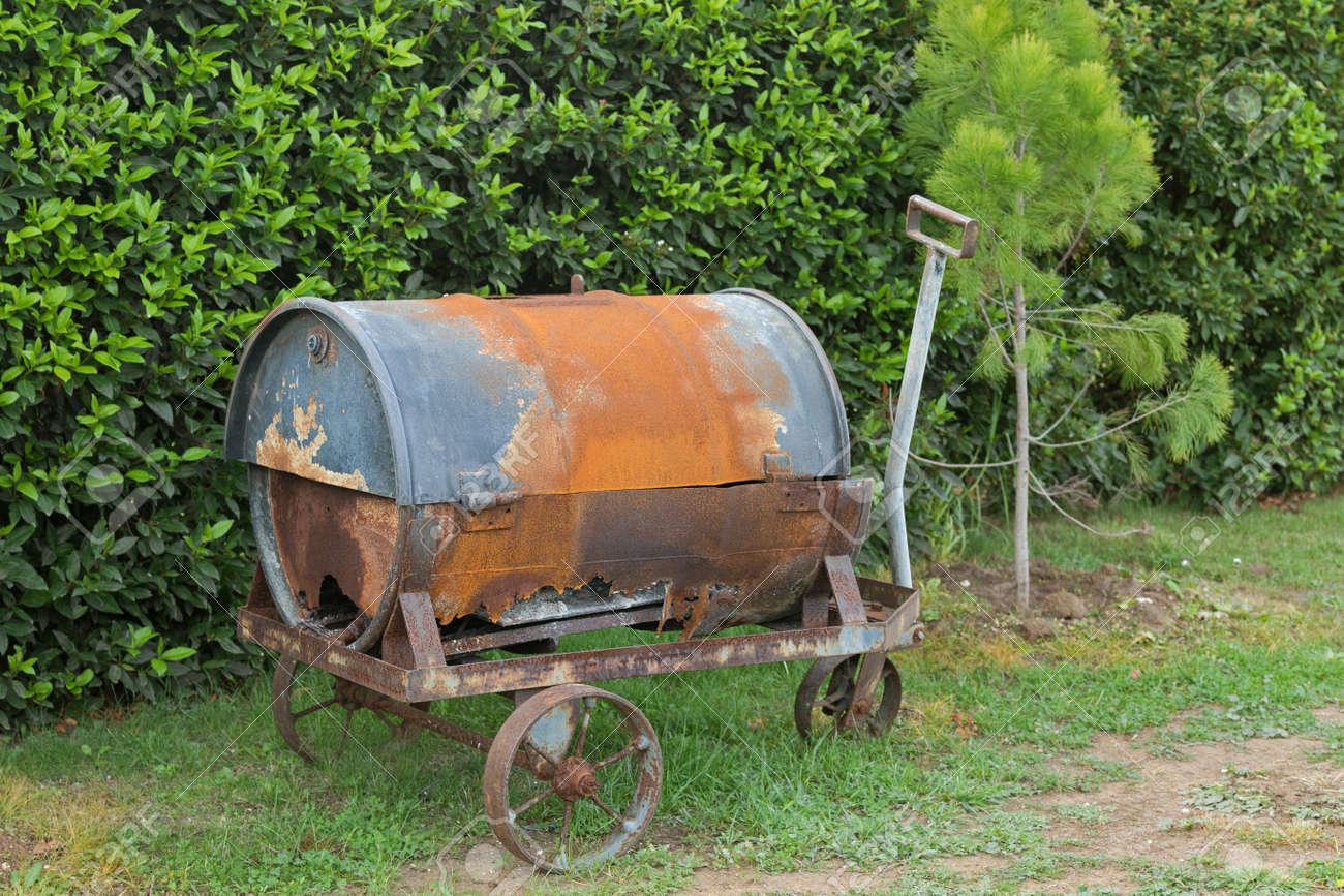 Carretilla De Metal Viejo Y Oxidado Con Viejo Barril En él Para Decorar El Jardín