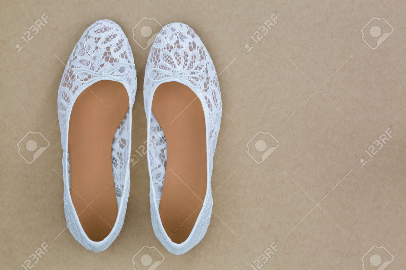 b3413c9a325 Stock Photo - Top view of popular white floral lace ballet flat slip on  shoes on brown background