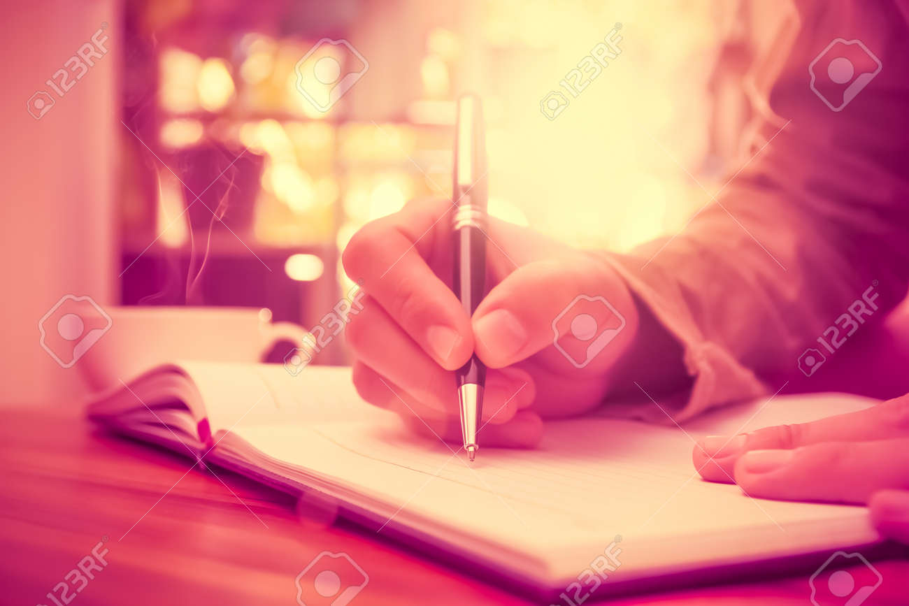 man hand holding a pen writing on the notebook stock photo man hand holding a pen writing on the notebook stock photo 44201294