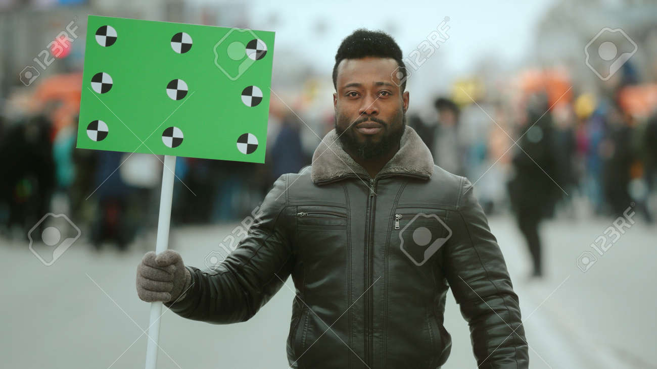 African american man. Empty banner placard. Track point. Blank board poster. Crowd people demonstration. Rebel strike protest. Revolution street. Real political rally - 150361428
