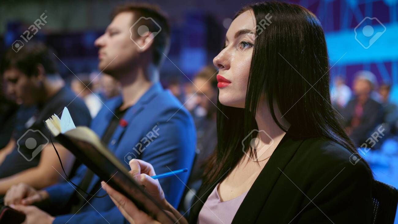 Girl write business note crowded forum audience. Viewer seminar listen speaker auditorium. Business woman writing in notepad financial summit. Group people learning education speech in crowd audience. - 156059690