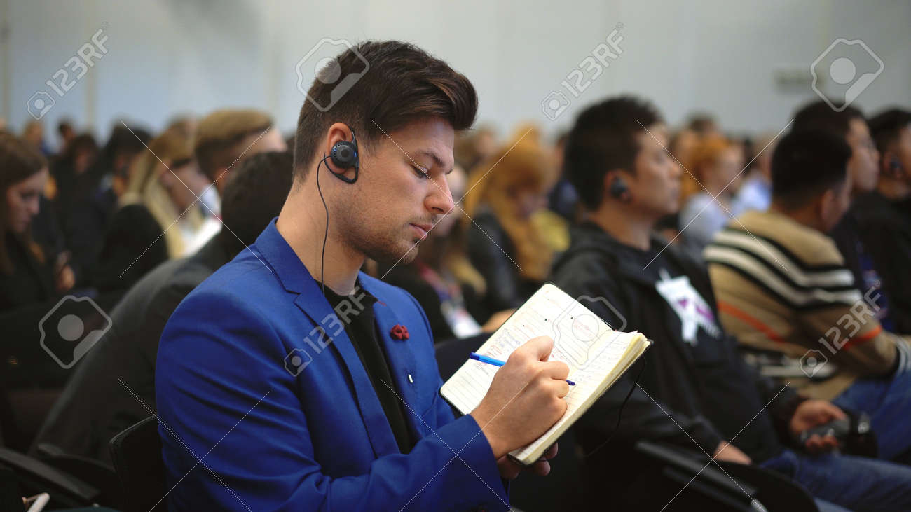 Crowd student study forum business man auditorium college. Education audience person write note. Studying crowded seminar writing notepad. Auditorium group people listen educational speech high school - 156059481