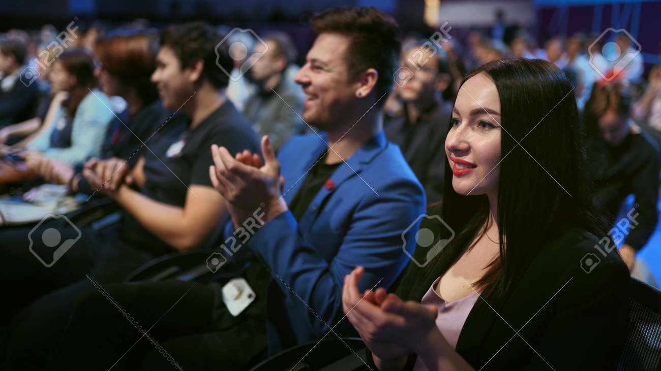 Seminar business meeting applause speaker. Crowd smiling audience active clapping man speech. Happy business woman applaud. Group smile people clap summit. Large auditorium joy applause economic forum - 156059624