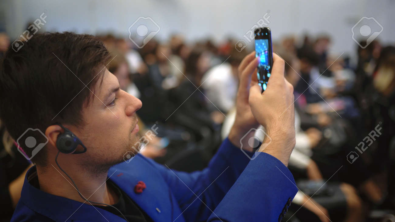 Person take photo on phone in crowded audience business forum. Conference business man with mobile. Seminar for viewer auditorium. group people listen speaker speech. Taking photography scene on phone - 156059684