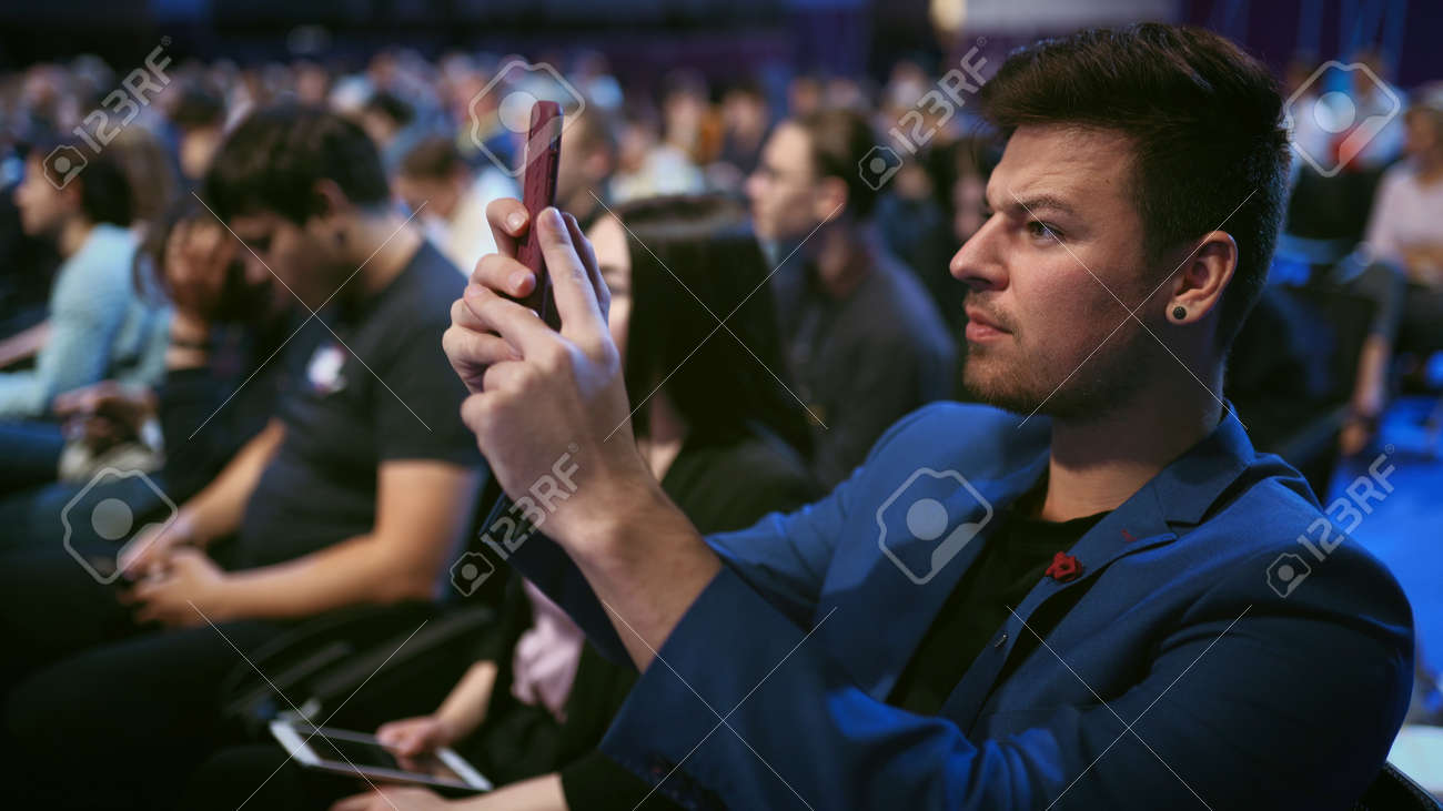 Person take photo on phone in crowded audience business forum. Conference business man with mobile. Seminar for viewer auditorium. group people listen speaker speech. Taking photography scene on phone - 156059552