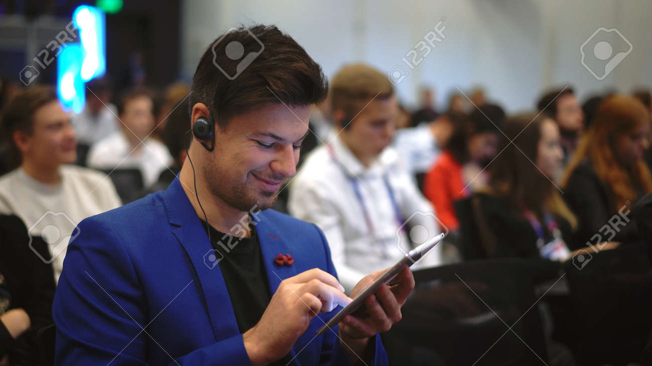 Person type touch screen crowded audience business forum. Viewer seminar listen speaker auditorium. Business man typing hand pad political summit. Group people learning speech in crowd audience. - 157271894