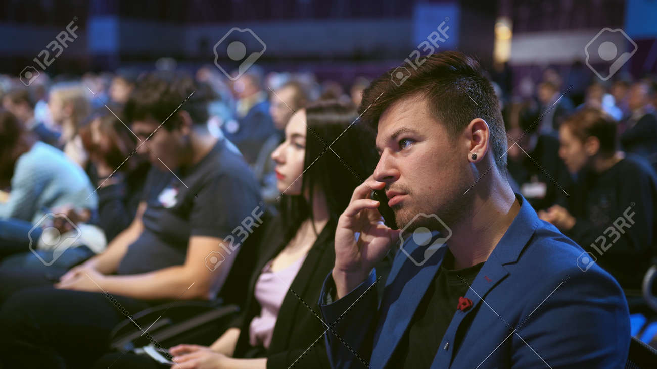 Business consultant talk on phone in crowd audience. Person negotiating on mobile in auditorium. Business man talking on phone economic forum. People discusses strategy partner in viewer audience. - 156059473