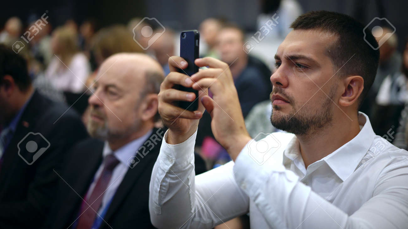 Person take photo on phone in crowded audience business forum. Conference business man with mobile. Seminar for viewer auditorium. group people listen speaker speech. Taking photography scene on phone - 156059531