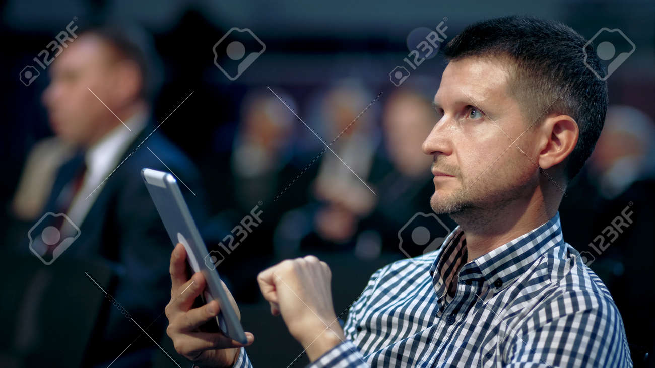 Person type touch screen crowded audience business forum. Viewer conference listen speaker auditorium. Business man typing hand pad economic summit. Group people learning speech in crowd audience. - 158502867