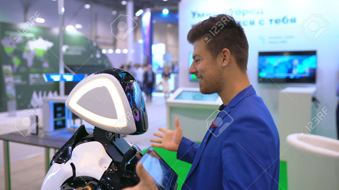 People in suit hugs robot loving closeup of greeting new friend 4K. An artificial intelligence bionic organism learn human behavior. A man enjoy hugging a tech cyborg for the friendship of the future. - 160842076