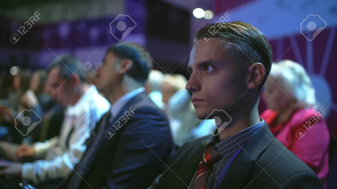 Russia, Novosibirsk, 21 sep, 2019: Crowd people listen speaker. Audience business meet forum. Auditorium viewer listen speaker. political summit business man. Group people listening speech crowd. - 156208845