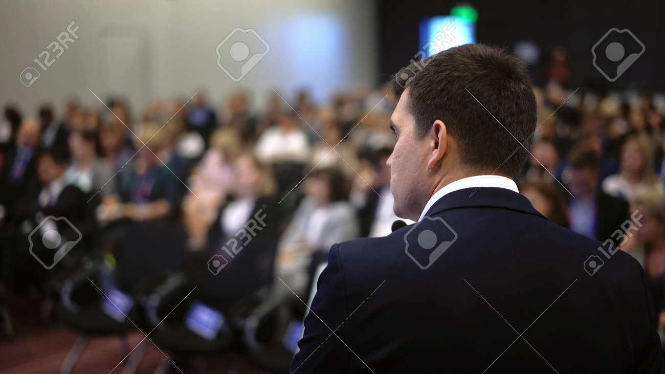 Speaker business meet talk audience from stage in microphone. Presenter economic forum speak public. Educational speech business man. Speaker talking group people at convention. Presentation men. - 156009683