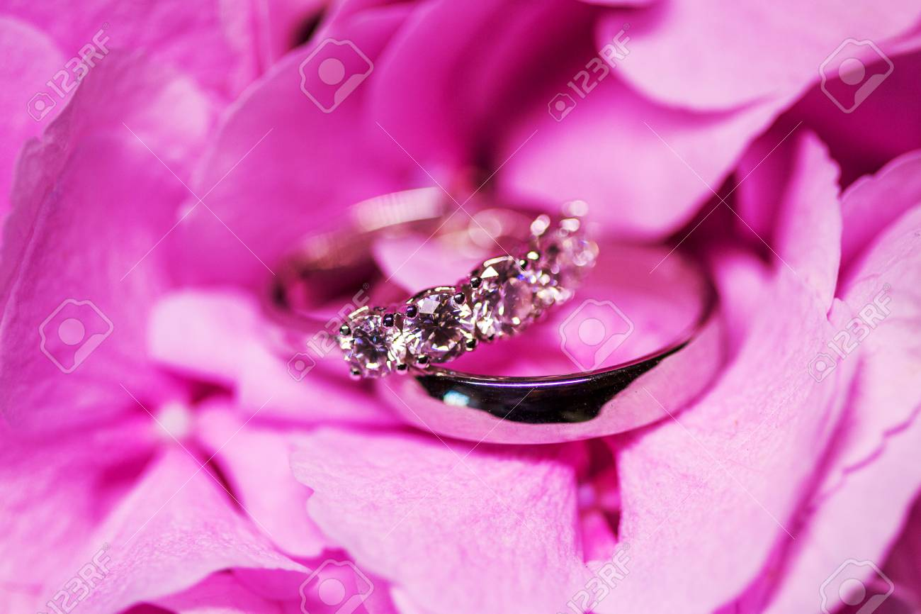 Golden Wedding Rings With Diamonds On The Tender Pink Flower. Stock ...