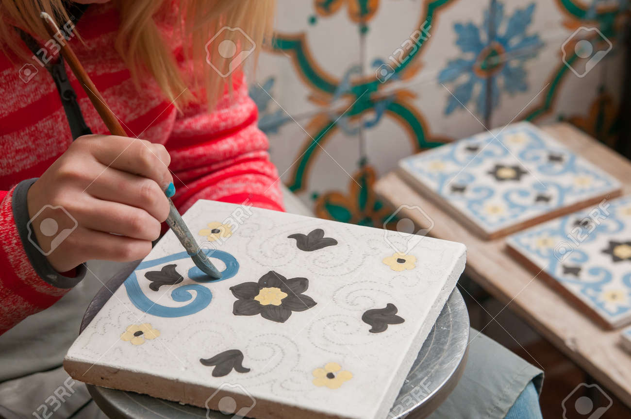 A pottery decorator painting a ceramic tile with floral motifs a pottery decorator painting a ceramic tile with floral motifs in his work table in caltagirone dailygadgetfo Images