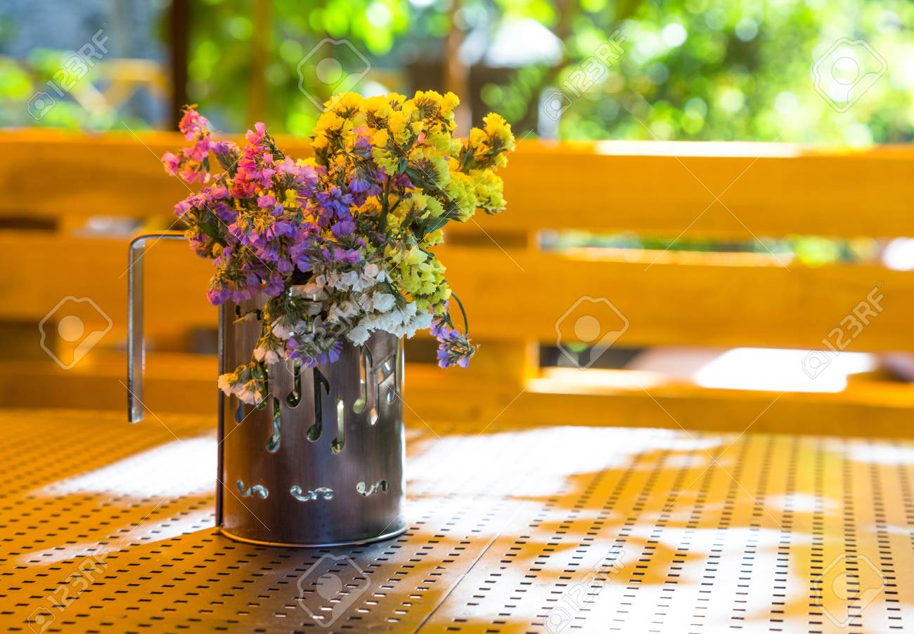 bunch of dry flowers in a cup standing on a table in the summer