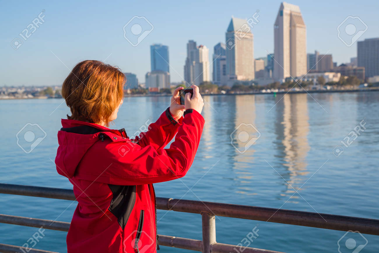 Young woman takes photos using smart mobile cell phone camera