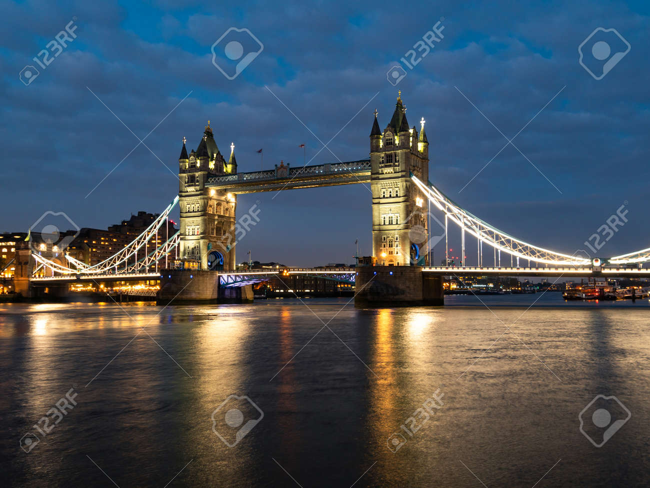 Tower Bridge at night illuminated by floodlights. Famous Tower Bridge in the evening with blue sky and reflex on water, London, England. Night cityscape with Tower Bridge, London, UK. - 132077374