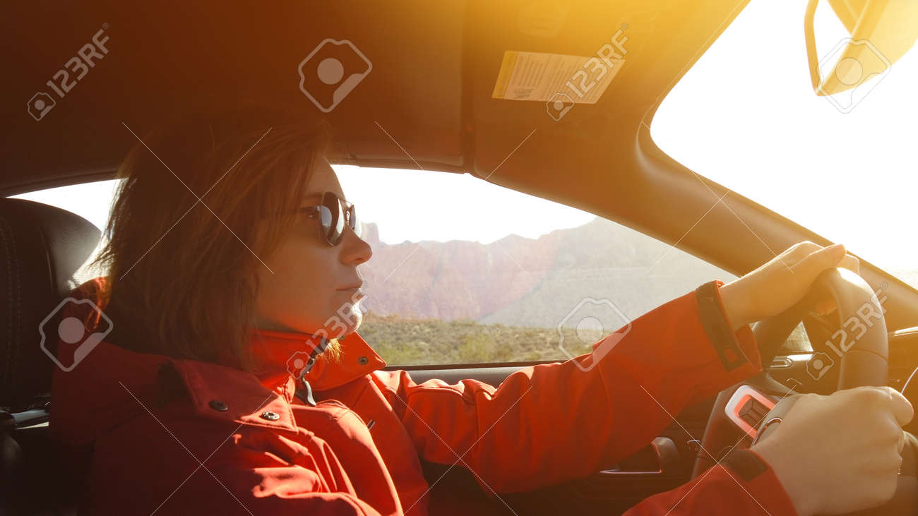Young woman is driving a car on a sunny day. - 148144918