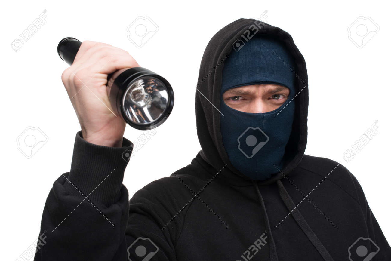 Scary theft with flashlight looking at the camera  Theft concept