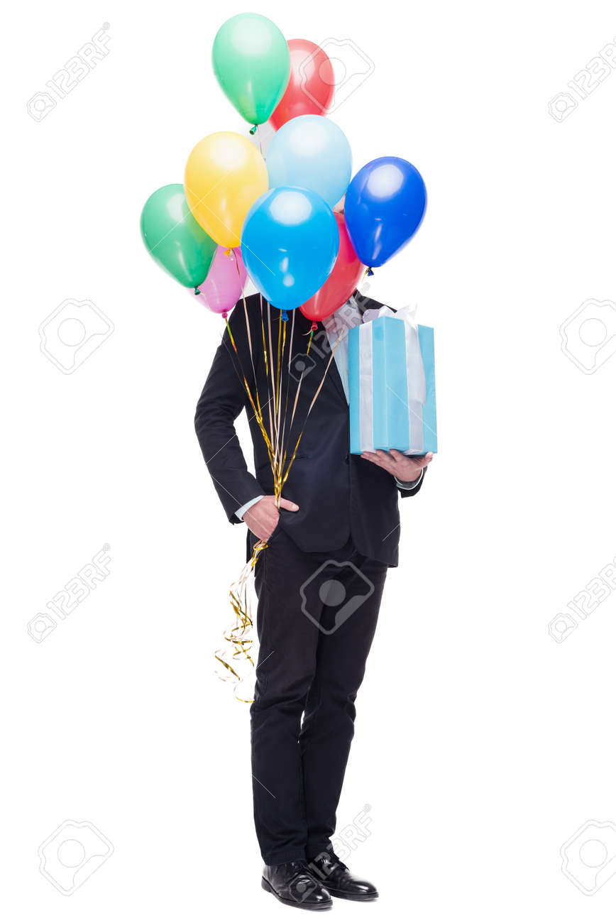 Funny Picture Of Young Man Hiding Behind Colourful Balloons Holding Present And Standing On