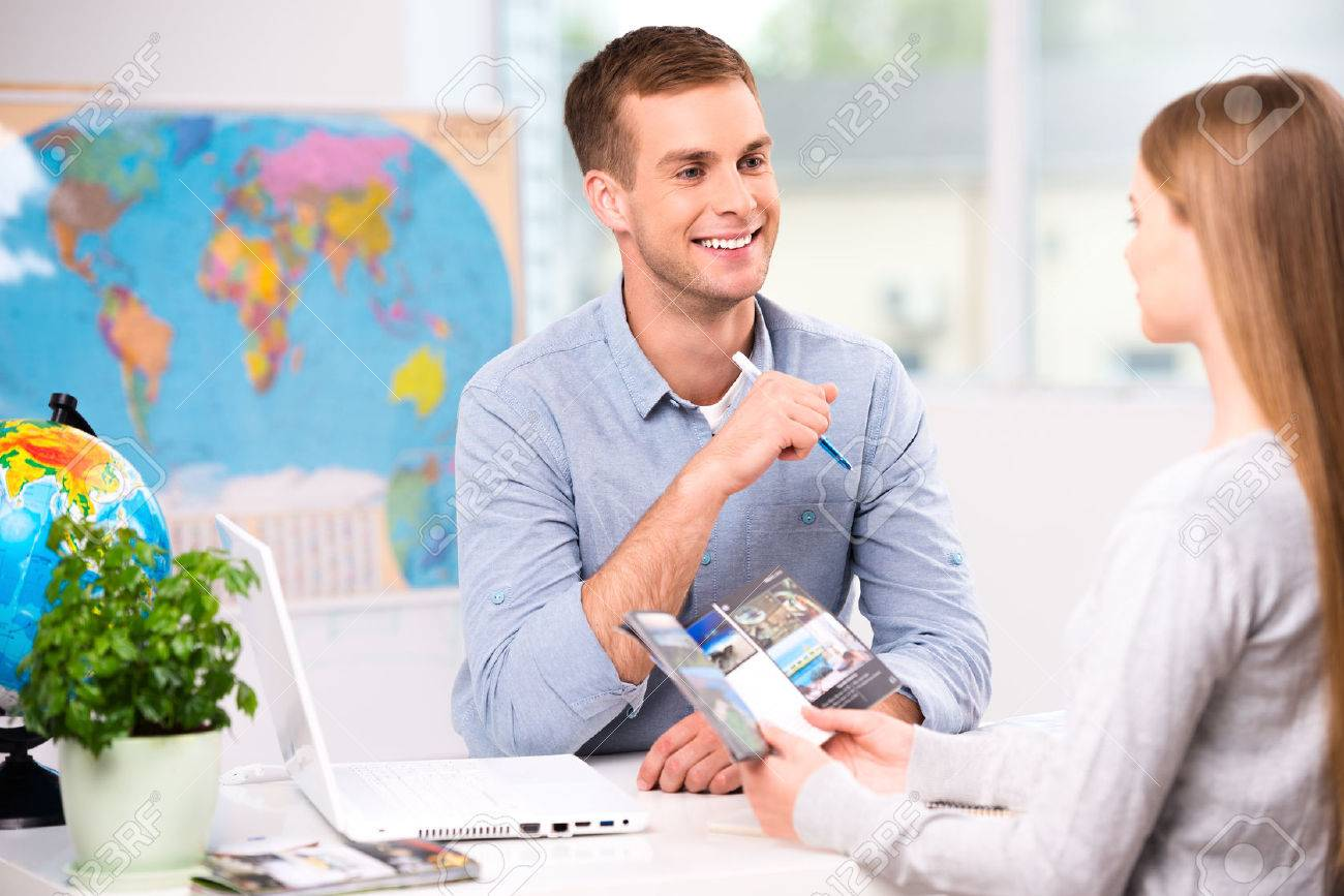 Photo of male travel agent and young woman. Young man smiling and offering vacation options for female tourist. Travel agency office interior with big world map Standard-Bild - 45644534