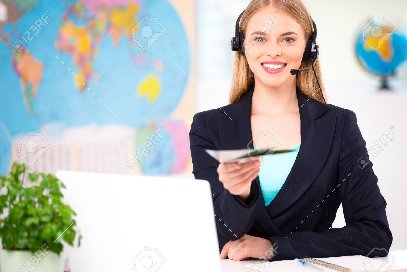 Photo of female travel agent  Young woman with headphones smiling,