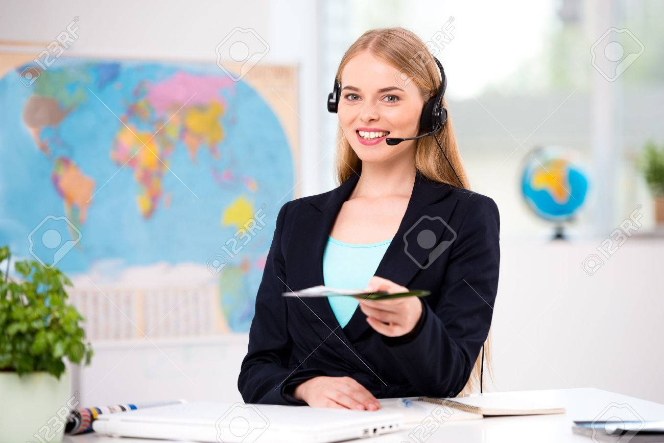 Photo of female travel agent. Young woman with headphones smiling, proposing tourist booklet and looking at camera. Travel agency office interior with big world map Standard-Bild - 45644555