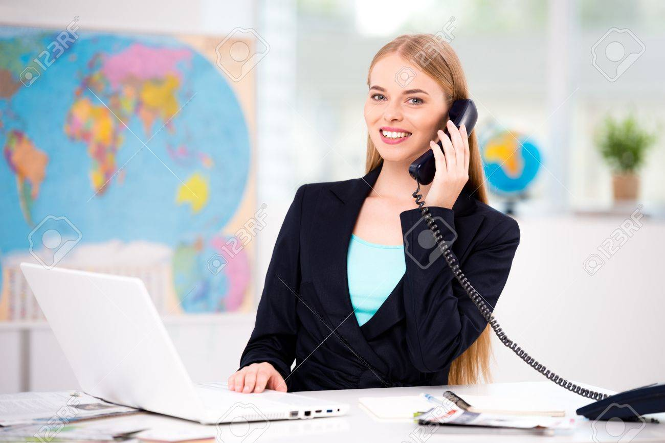 Photo of female travel agent. Young woman talking on phone, smiling and looking at camera. Travel agency office interior with big world map Standard-Bild - 45644554