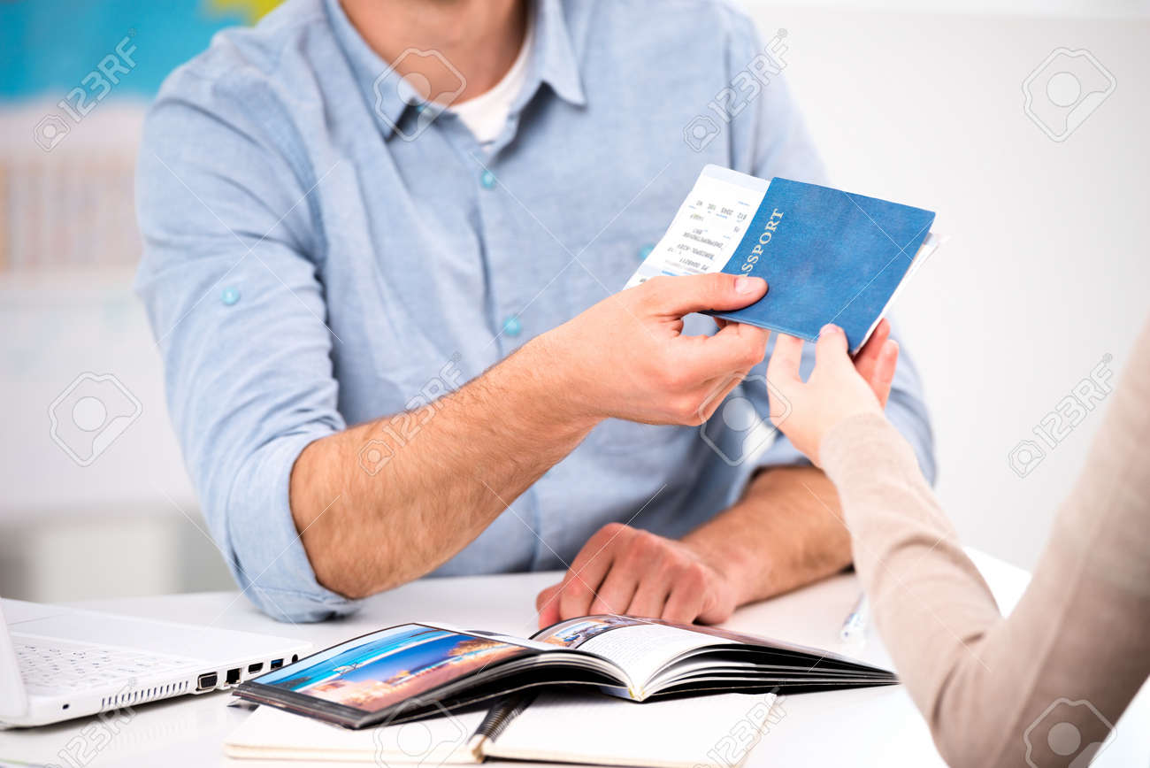 Close up photo of male travel agent and young woman. Young man giving tickets and passport with visa to female tourist Standard-Bild - 45644661