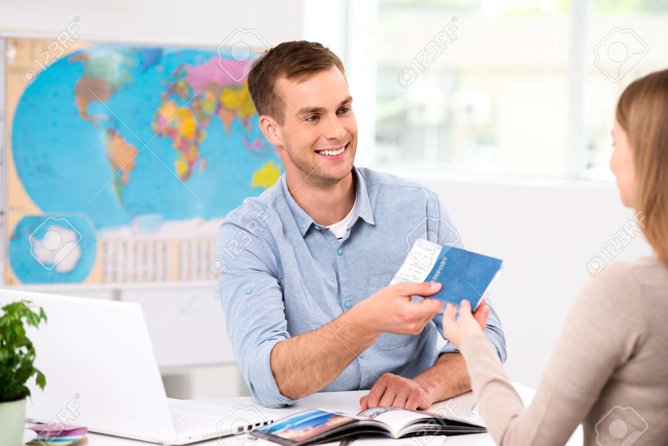 Photo of male travel agent and young woman. Young man smiling and giving tickets, passport with visa to female tourist. Travel agency office interior with big world map Standard-Bild - 45644662