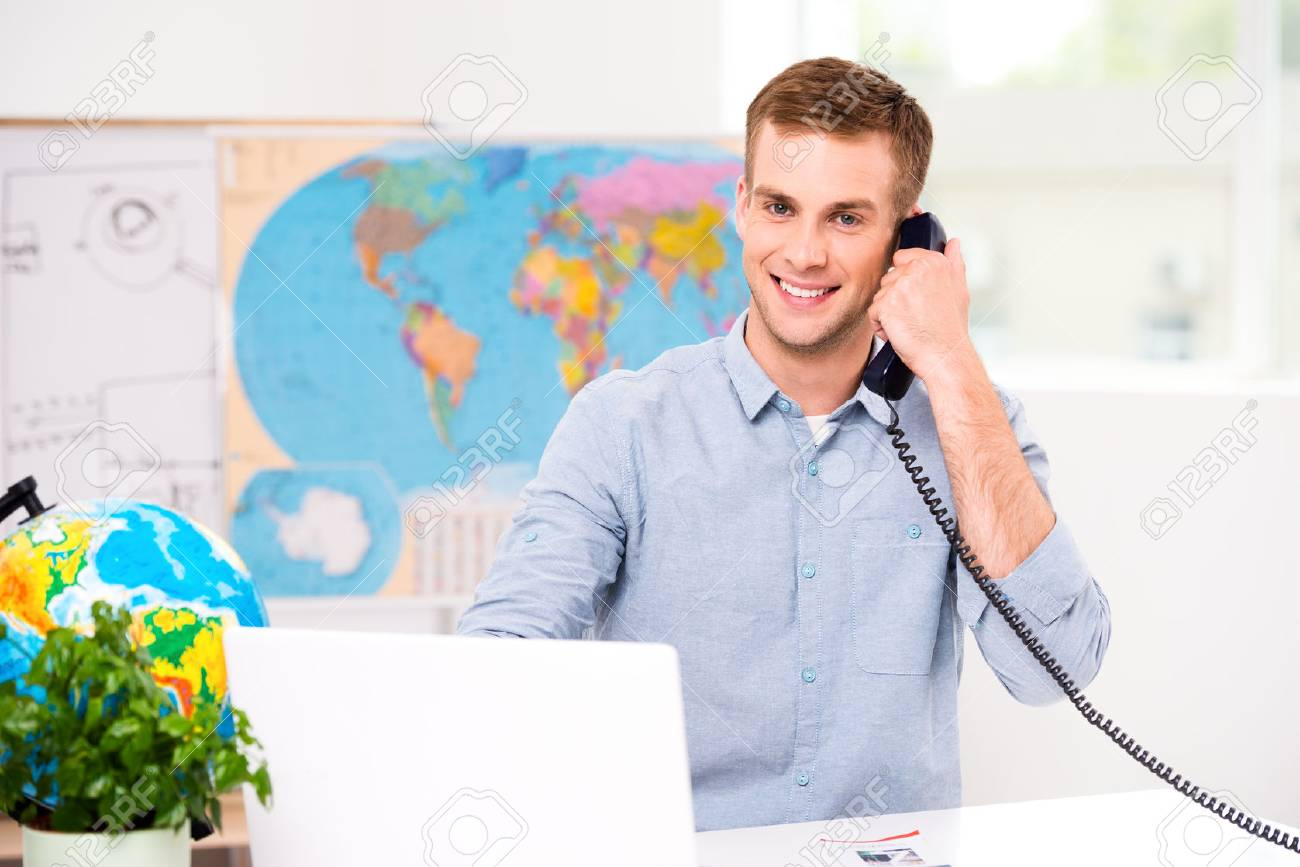 Photo Of Male Travel Agent. Young Man Talking On Phone, Smiling.. Stock  Photo, Picture And Royalty Free Image. Image 45644842.