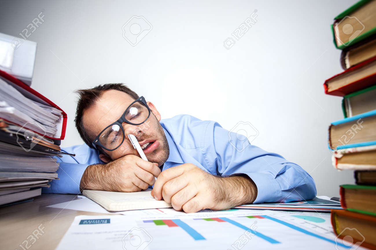 Funny photo of businessman with beard wearing shirt and glasses. Overworked businessman sleeping at table full of documents with pen in his nose. Isolated on white background Standard-Bild - 46697258