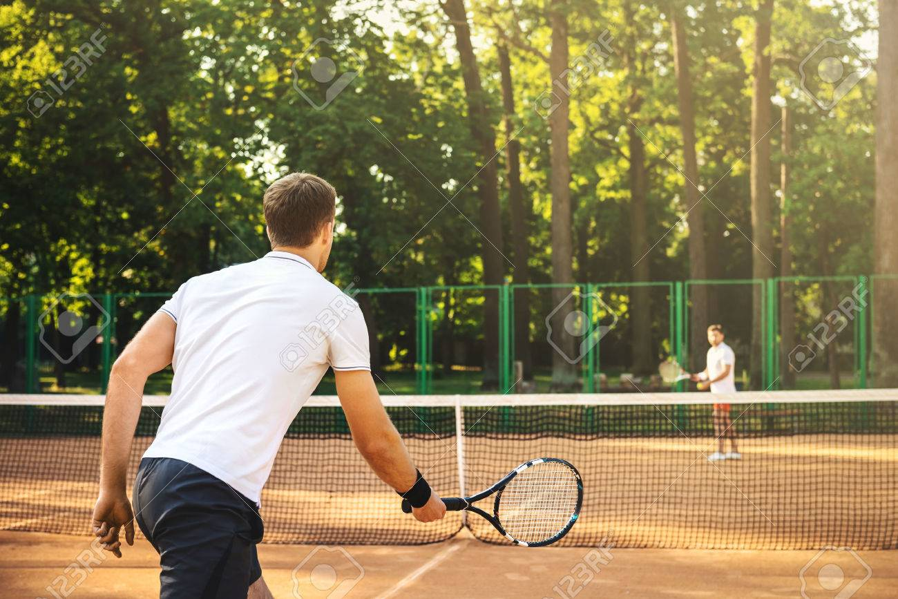 Picture of handsome young men on tennis court. Men playing tennis. Man is ready to hit tennis ball. Beautiful forest area as background Standard-Bild - 46697317