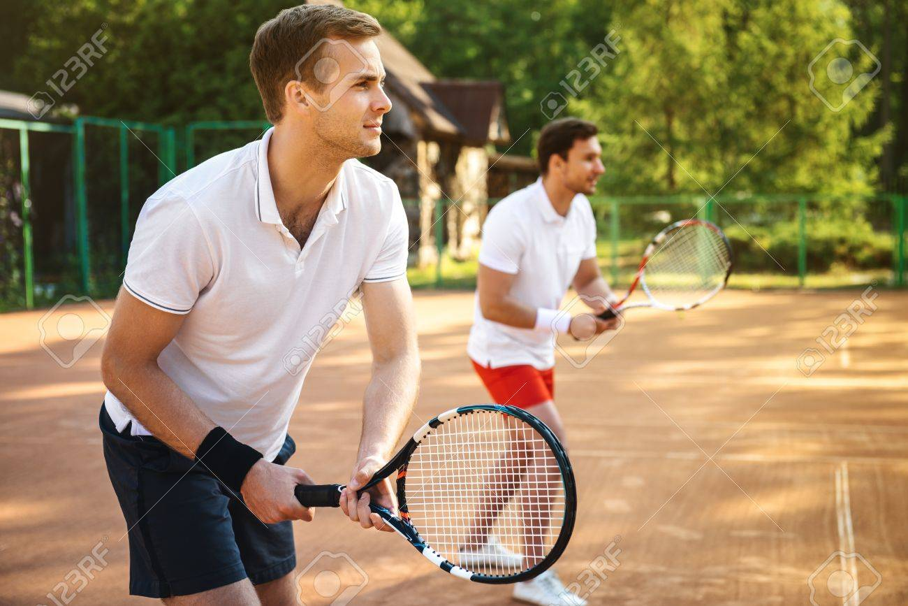 Picture of handsome young men on tennis court. Men playing tennis. Man is ready to hit tennis ball. Beautiful forest area as background Standard-Bild - 46697322