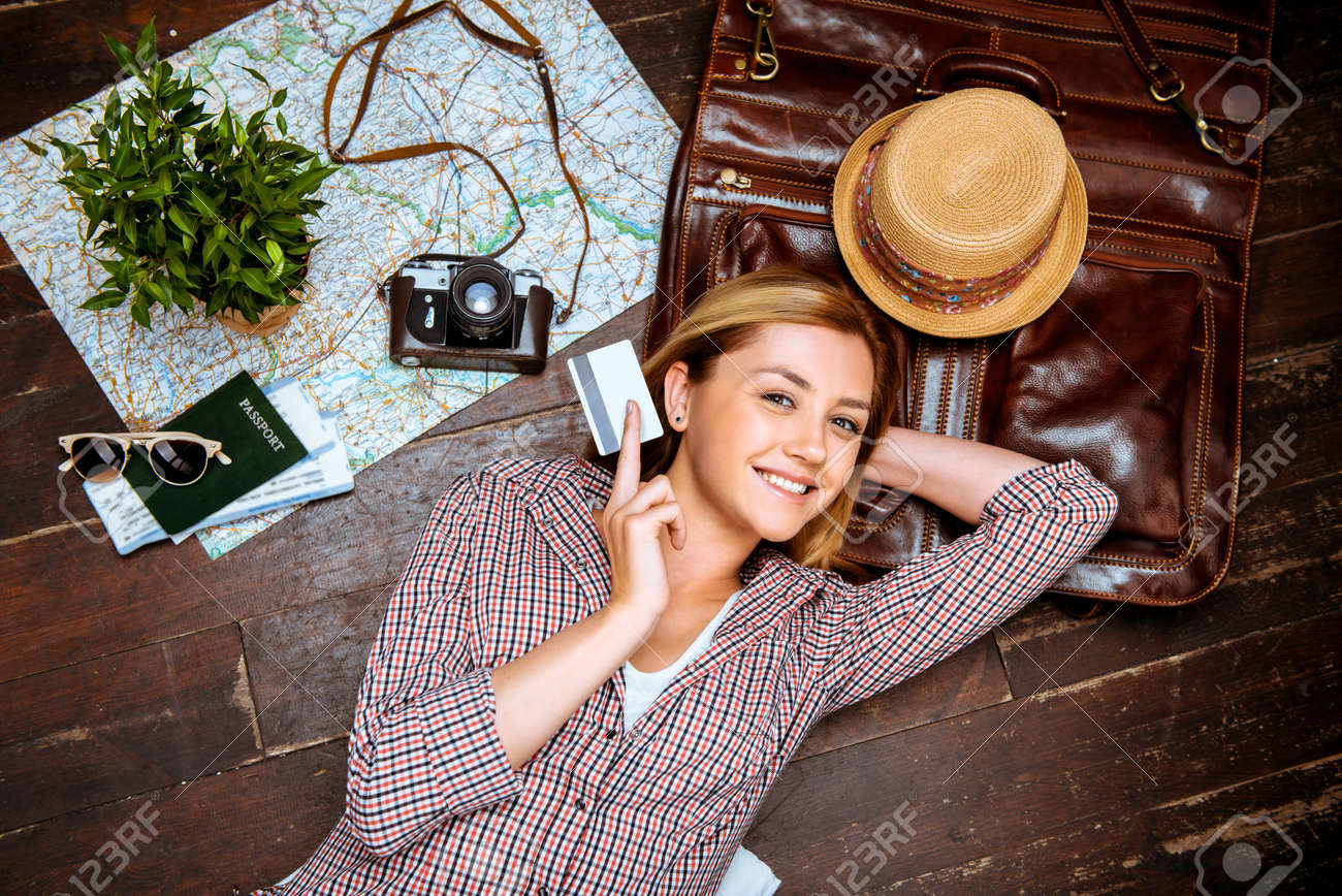 Top view photo of beautiful blonde girl lying on wooden floor. Young woman smiling, holding credit card and looking at camera. Passport, tickets, vintage camera, hat and map are on floor Standard-Bild - 46697408