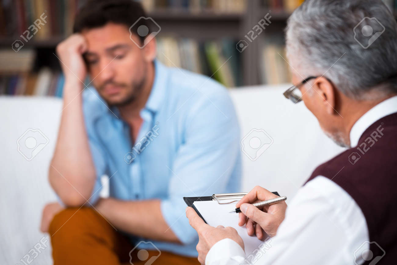 Sad young man talking with psychologist. Psychologist taking notes. There are many books in psychologist office Standard-Bild - 46699458