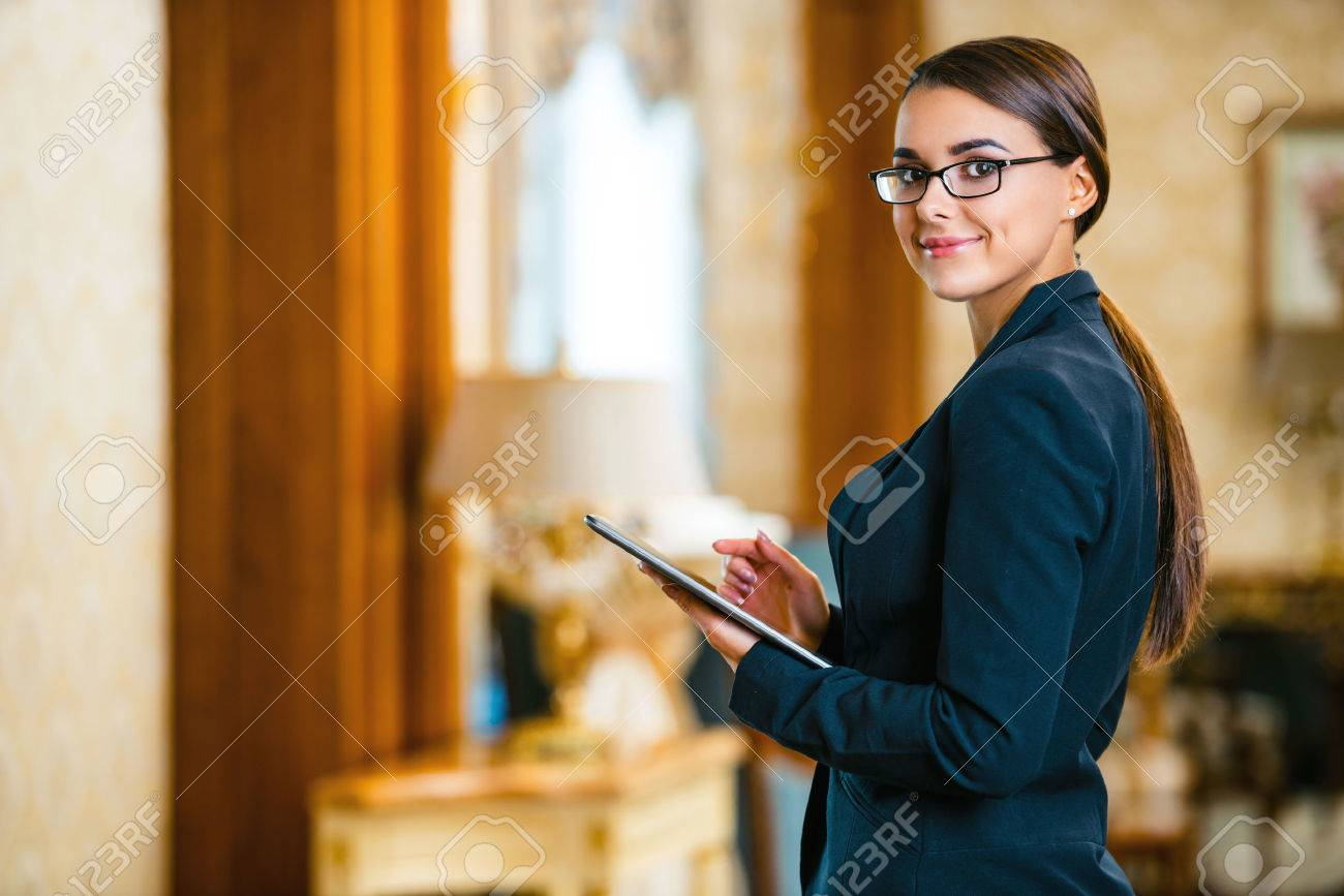 Young business woman wearing suit and glasses, standing in nice hotel room, using tablet computer and looking at camera Standard-Bild - 47354650