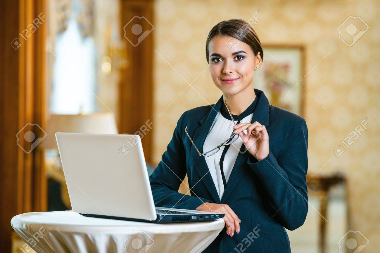 Young business woman wearing suit, standing in nice hotel room, using laptop and looking at camera Standard-Bild - 47354682