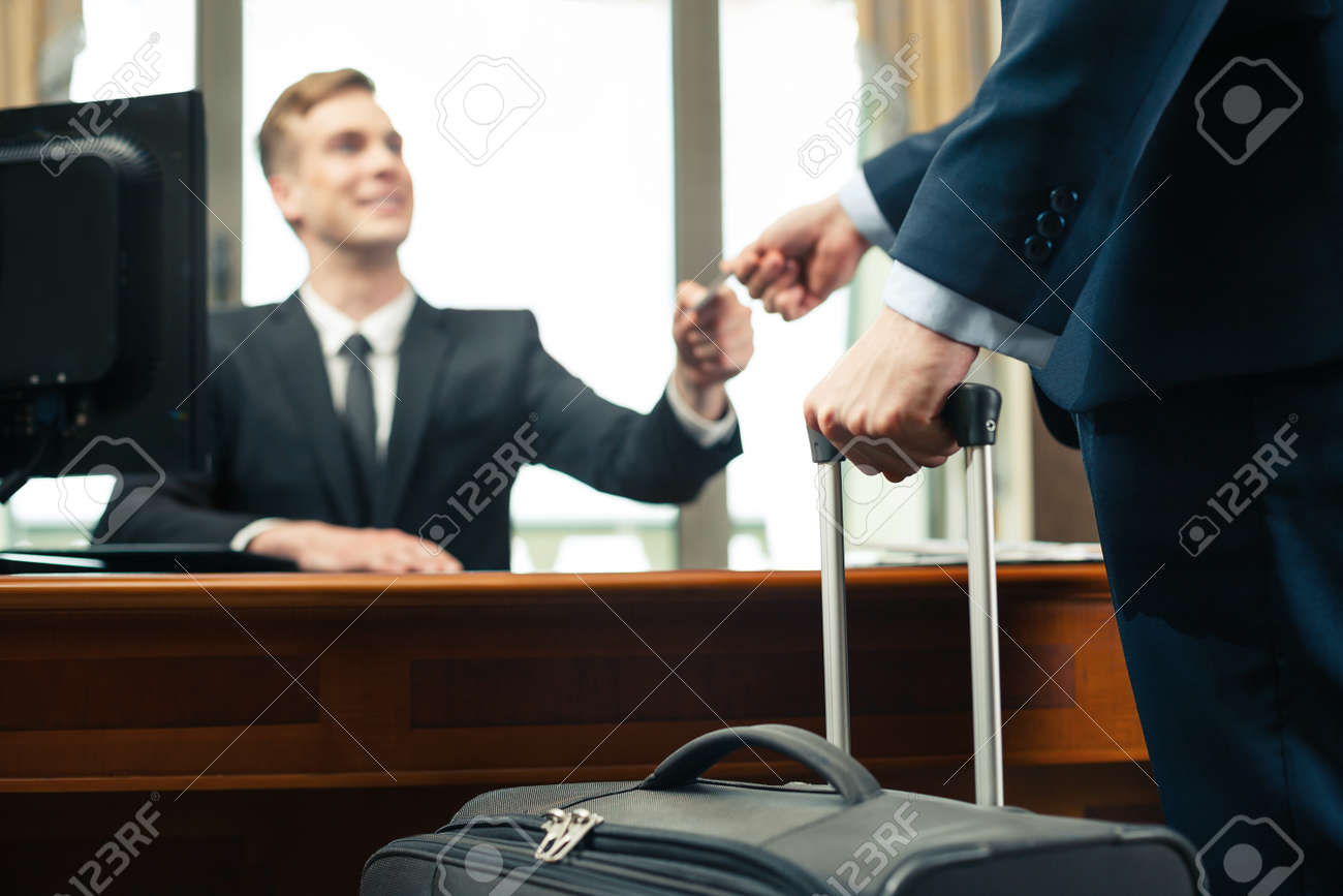 Customer with suitcase giving his credit card to receptionist Standard-Bild - 47354513