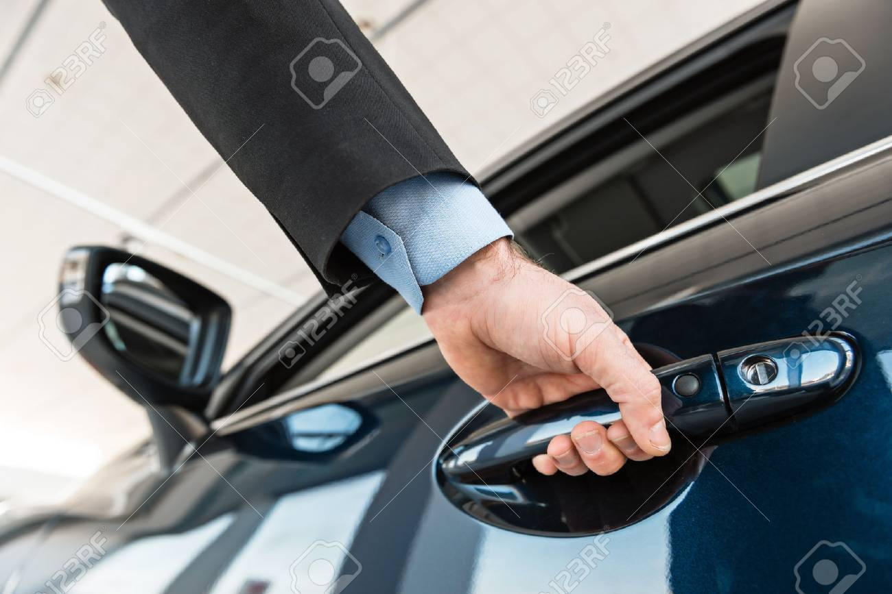 Close up photo of young man hand touching and openning new car. Concept for car rental Standard-Bild - 47712658