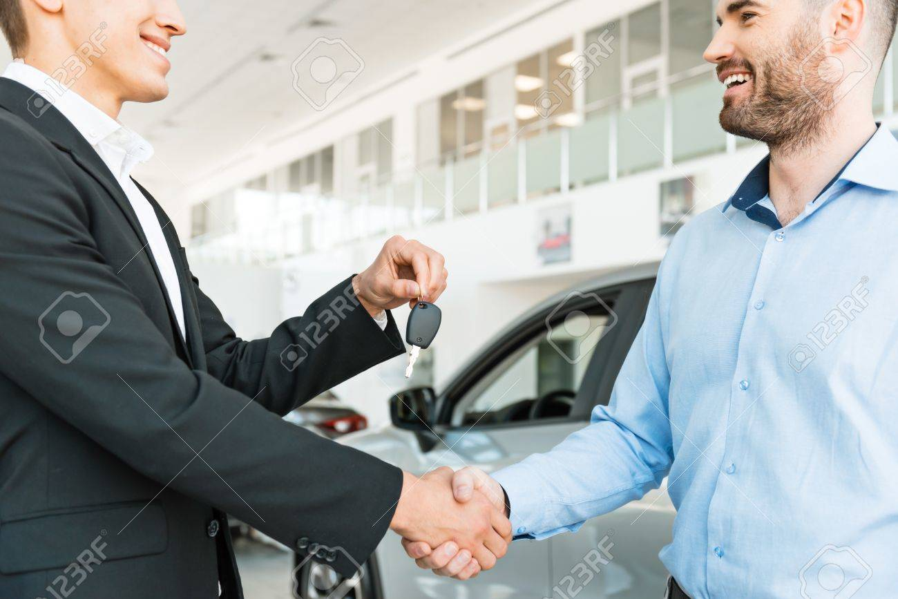 Photo of young male consultant giving car key to buyer after successful deal in auto show. Concept for car rental Standard-Bild - 47712702