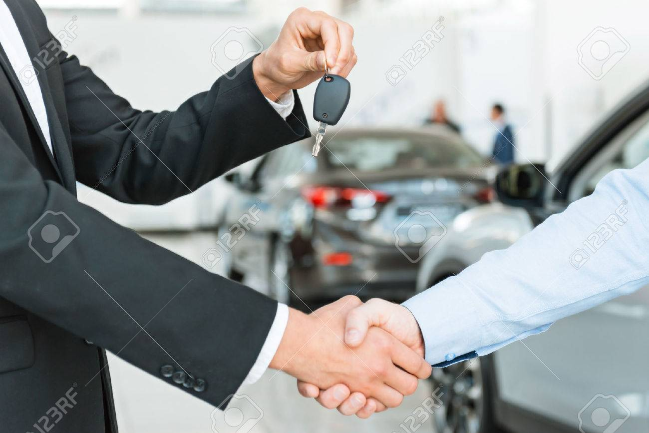 Photo of young male consultant giving car key to buyer after successful deal in auto show. Concept for car rental Standard-Bild - 47712703