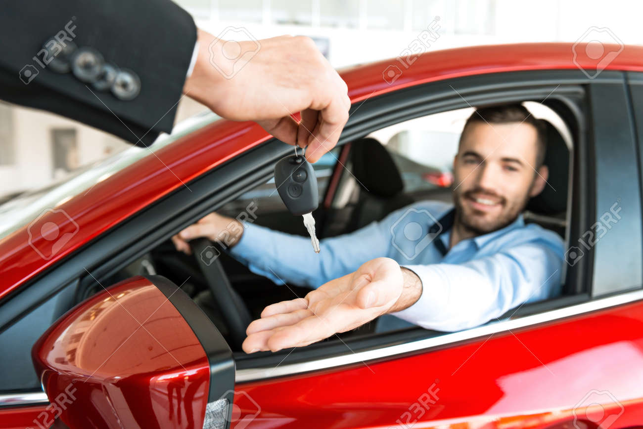 Photo Of Young Man Sitting Inside New Car And Getting Keys To It. Concept  For