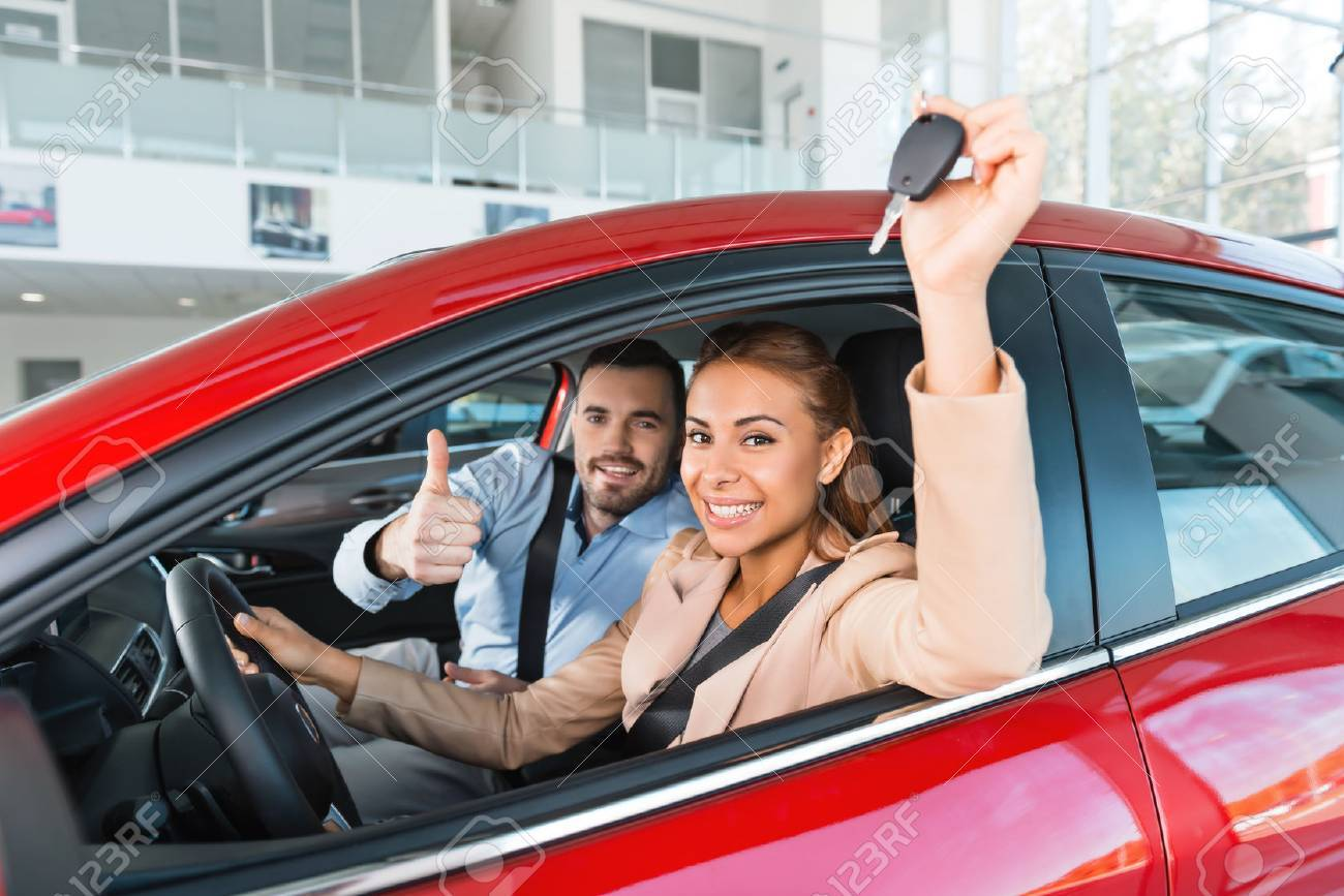 Photo of young couple sitting inside new car. Woman holding keys to it. Man smiling and showing thumb up. Concept for car rental Standard-Bild - 47712884