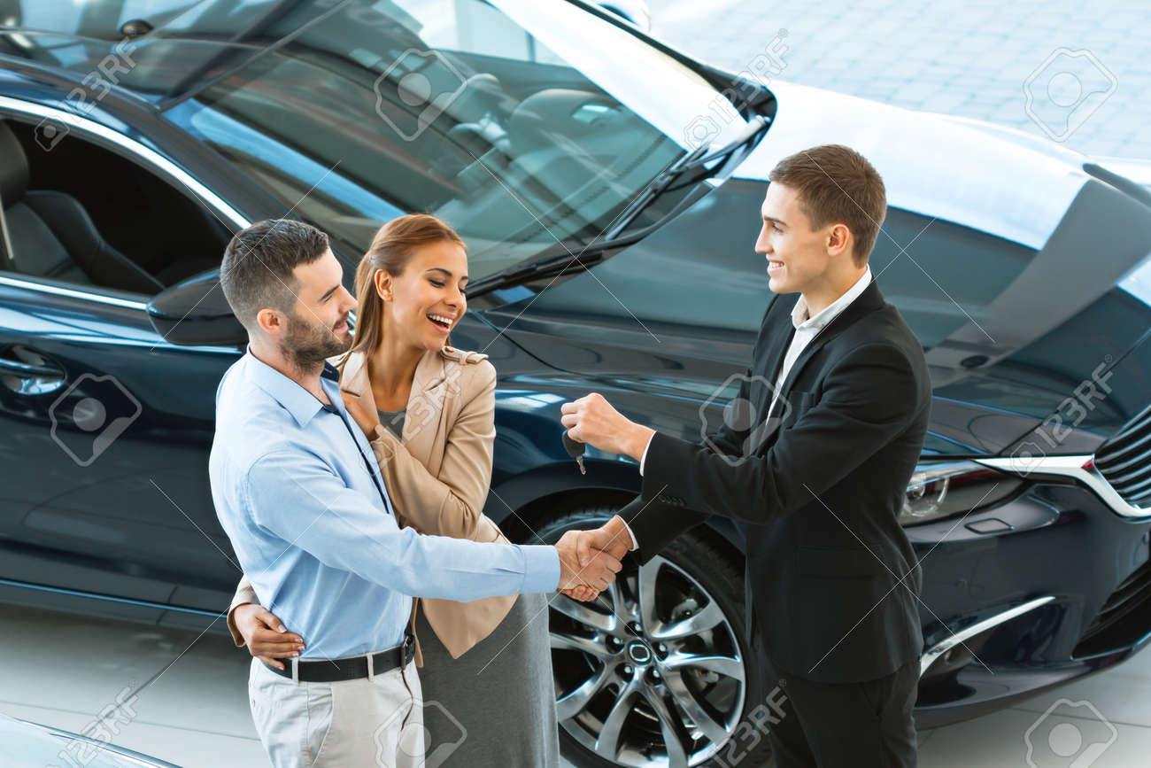 Top view photo of young male consultant giving car key to buyers after successful deal in auto show. Concept for car rental Standard-Bild - 47714419