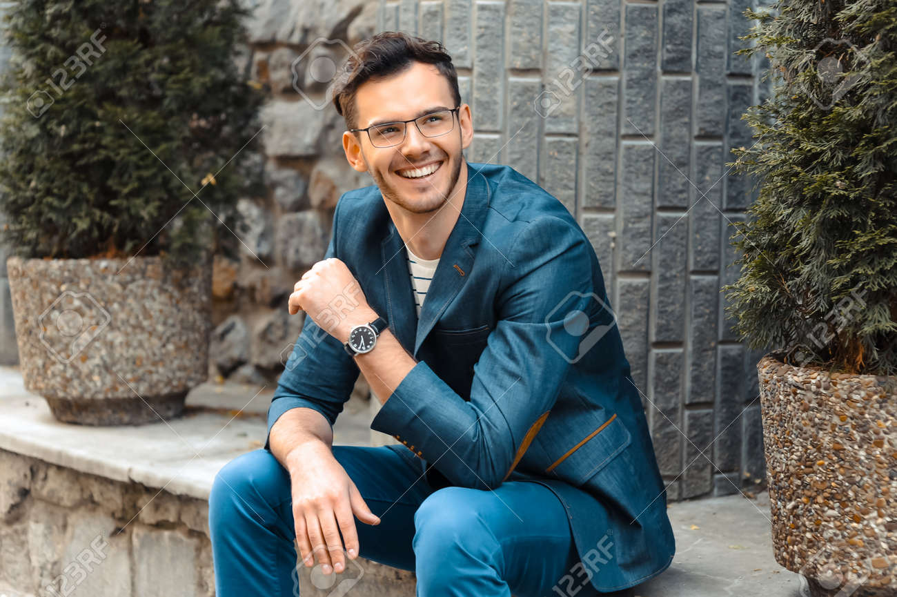 Portrait of stylish handsome young man with bristle standing outdoors. Man wearing jacket and watch. Man with glasses cheerfully smiling Standard-Bild - 47873954